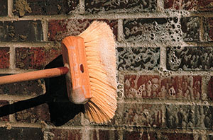 A masonry cleaner is gently agitated by brush. Note that the brush bristles are non-metallic, so as not to react with the cleaner and stain the masonry.