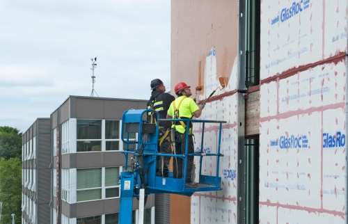 Installers from Katwall Inc roller-apply Cat 5 Primary Air & Waterproof Barrier over sheathing sealed with pink Joint & Seam Sealer and red FastFlash, for a continuous, seamless, durable, vapor-permeable barrier to air and water leakage through the building envelope at Seattle's Bullitt Center. John Stamets photo
