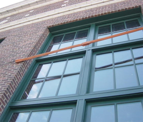 JE Dunn cleaned the masonry via the traditional bucket-and-brush method  to protect these painstakingly replicated historic wood windows. Note the bottom edges of the terra cotta trim, now free of its black soiling.