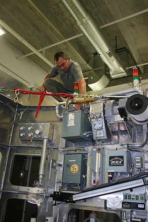 Ron Tatley makes some adjustments to the Design Verification Test Chamber he developed to test the air- and water-tight integrity of wall assembly mock-ups. PROSOCO photo