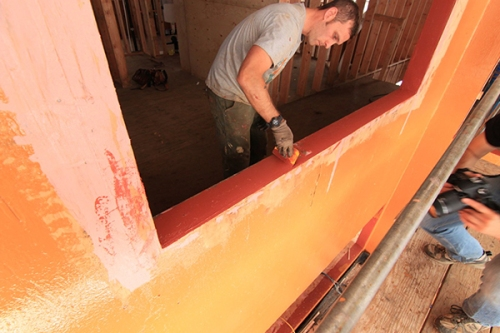An installer seals a rough opening with an STPE-based flashing at an under-construction passive house in Yamhill County, Ore. The builders chose the fluid-applied flashing because of demonstrated performance in stopping air leaks through the building envelope. Photo courtesy Hammer and Hand