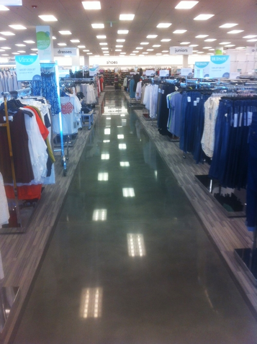 Clothing waits for shoppers like low-hanging fruit along a polished concrete aisle